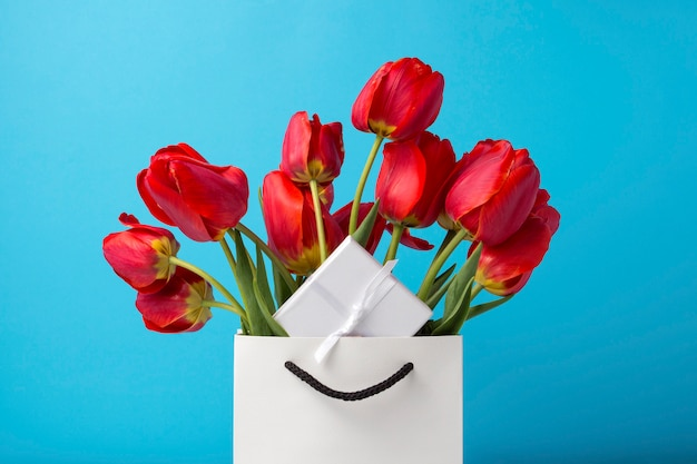 Bouquet of brightly red tulips in a white gift bag on a blue background. conception of congratulations, surprise and gift