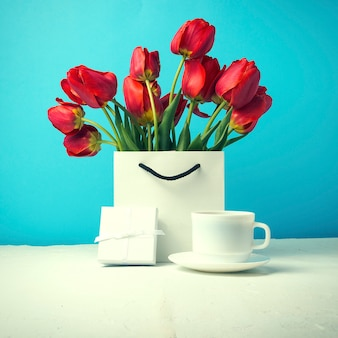 Bouquet of brightly red tulips in a white gift bag, white cup with coffee, white gift box on a blue. concept congratulations, surprises and gifts