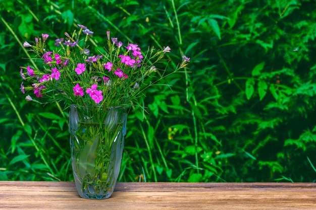 Bouquet of carnations in a glass vase on a green natural background with copy space