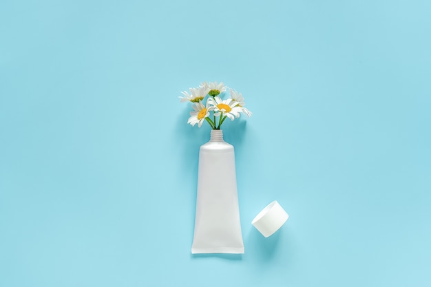 Bouquet of chamomile flowers from cosmetic, medical white tube for cream, ointment, toothpaste or other product