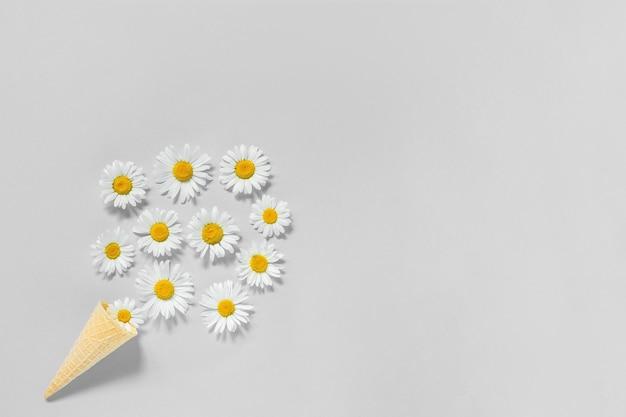 Букет цветов ромашки в вафельном рожке мороженого на сером цветном фоне. модные цвета 2021 года. копирование пространства плоская планировка вид сверху концепция привет, лето.