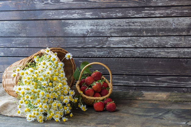 A bouquet of chamomiles in a wicker basket and strawberries in a small basket