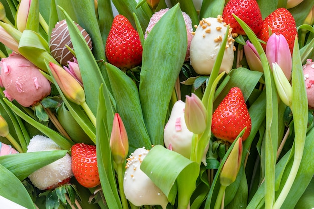 Bouquet of chocolate covered strawberries and tulips on green background