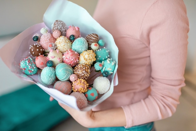 A bouquet of chocolate covered strawberries in woman hands