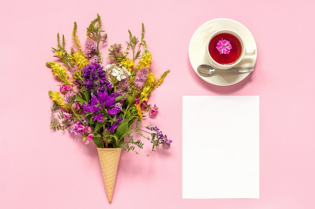 Bouquet colored flowers in ice cream waffle cone, cup of tea and blank paper card