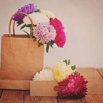 Bouquet of colorful asters in paper bag with empty greeting card for text. toned image