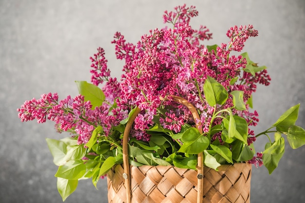 Bouquet of colorful lilac flowers in a wicker basket on concrete background