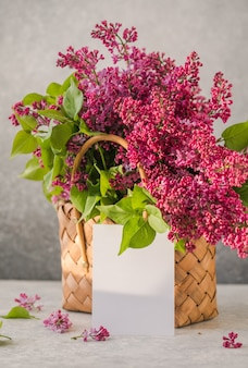 Bouquet of colorful lilac flowers in a wicker basket and a white paper on concrete background