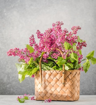 Bouquet of colorful lilac flowers in a wicker basket