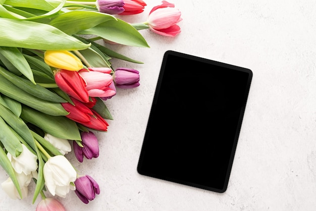 Bouquet of colorful tulip flowers and digital tablet top view flat lay