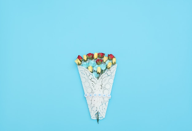 The bouquet of craft flowers wrapped in a white lace bundle on blue background.