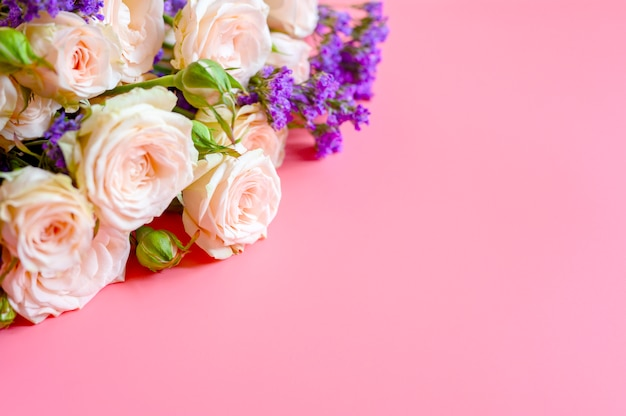 A bouquet of cream roses and bright purple flowers in full bloom on pink