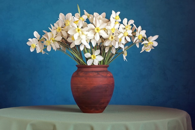 Bouquet of daffodils in a clay jug on a blue .