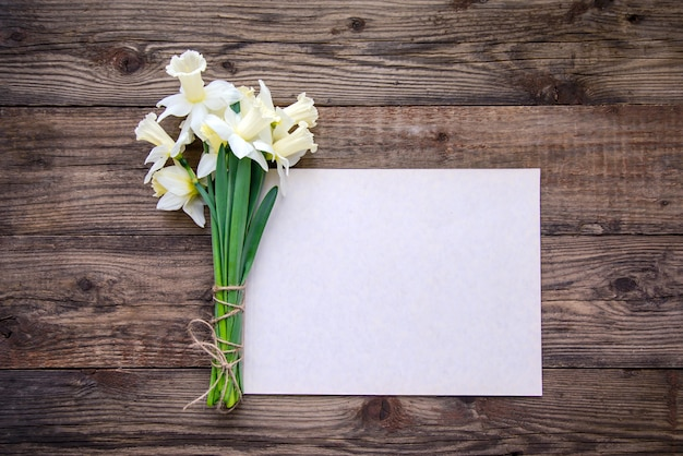 A bouquet of daffodils and a piece of paper on a wooden background