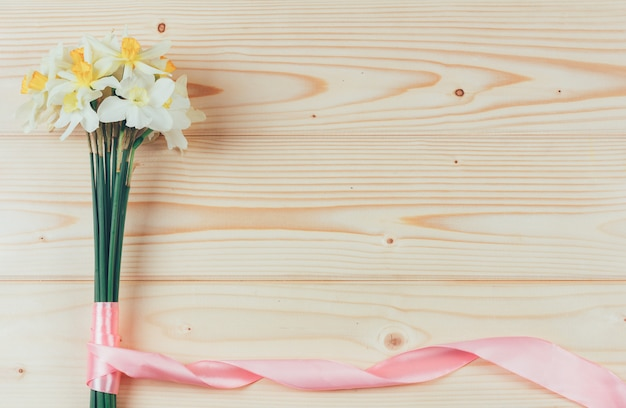 Bouquet of daffodils with pink ribbon on wooden  with copyspace