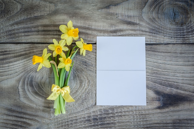 Bouquet of daffodils on wooden table with white card.