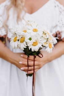 Bouquet of daisies in the hands of the bride on the background of a white dress