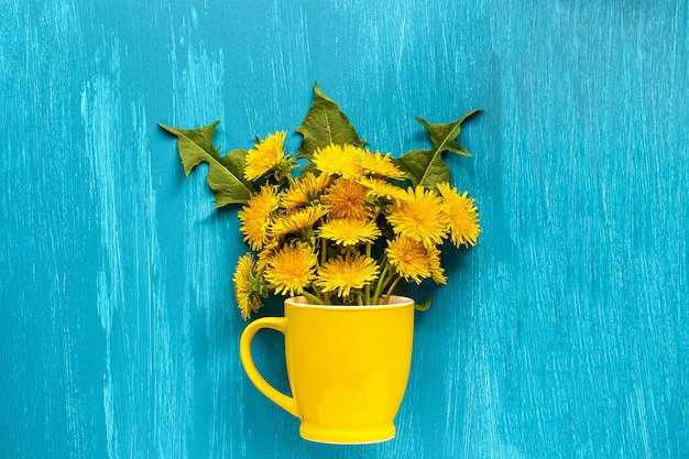 Bouquet dandelions taraxacum flowers in yellow mug