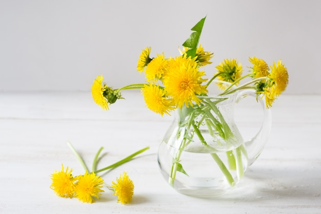 A bouquet of dandelions in white vase on a white wooden background
