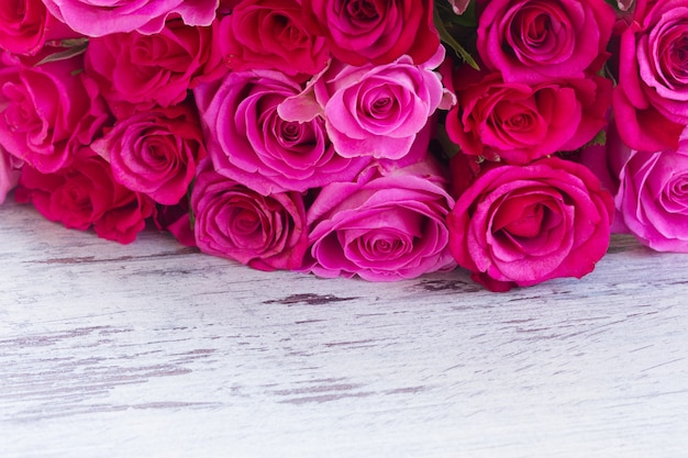 Bouquet of dark and light pink fresh roses border on white wooden aged background