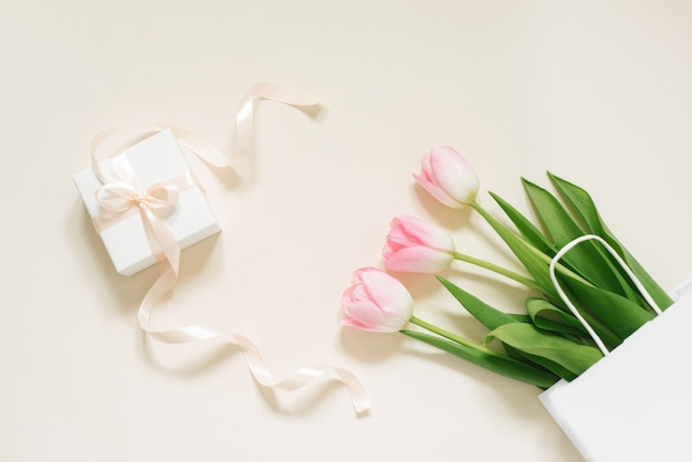 Bouquet of delicate tulips and a white box gift with a bow on an beige background, floral festive arrangement of flowers