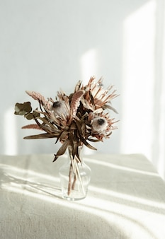 A bouquet of dried flowers in a glass vase on a light background with sunlight.