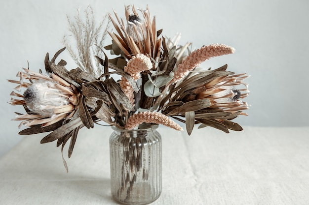 A bouquet of dried flowers in a glass vase on a light background.