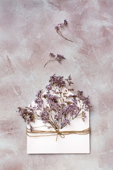 A bouquet of dried flowers in a light envelope tied with a rope on a textured background. greeting romantic card. top and vertical view