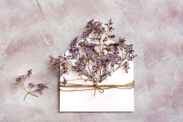 A bouquet of dried flowers in a light envelope tied with a rope on a textured background. greeting romantic card. top view
