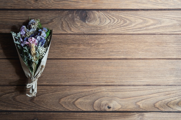 Bouquet of dried wild flowers on rustic wooden table background