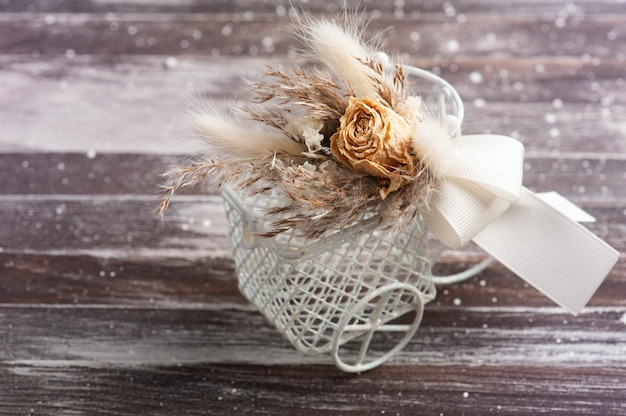 Bouquet of dry flowers on decorative bike on rustic table. greeting card for wedding or holiday in natural tones