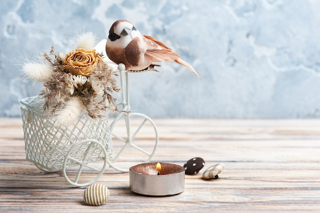 Bouquet of dry flowers on decorative bike with litle brown bird and lit candle on the table. greeting card for wedding or holiday in natural tones with copy space