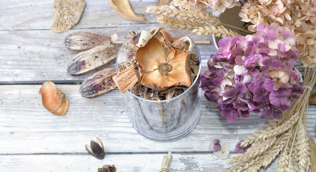 Bouquet of dry flowers and potpourri in a glass jar on a white table
