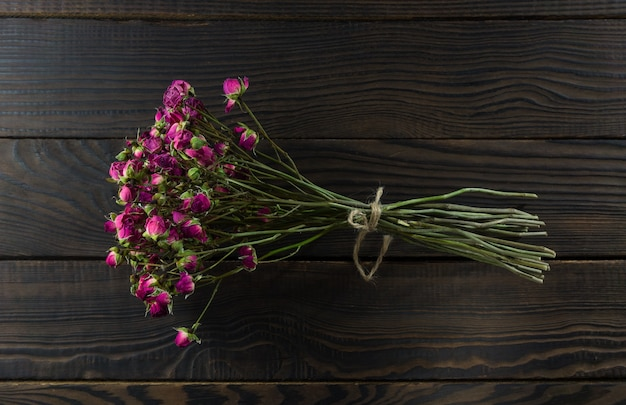 Bouquet of dry flowers with a ribbon on the dark wooden surface.
