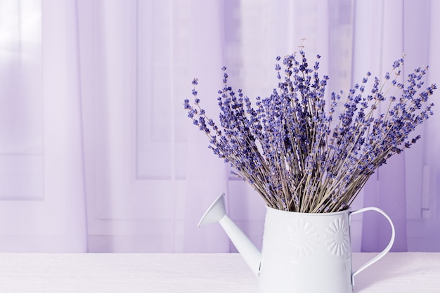 Bouquet of dry lavender in watering can about window on white table.