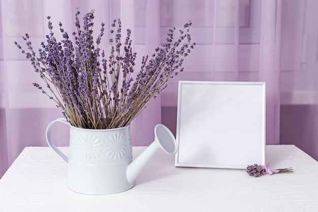 Bouquet of dry lavender in watering can with picture frame mock-up about window on white table. soft focus.