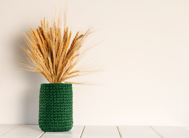 Bouquet of dry wheat and rye in a green knitted vase on a white wall