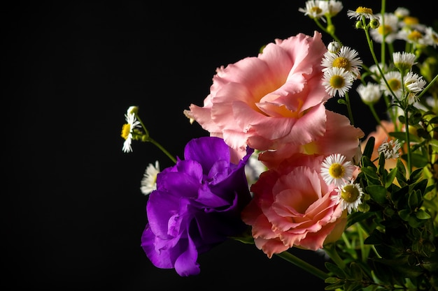 Bouquet of eustoma with boxwood and small-leaved branches on a table on a black background