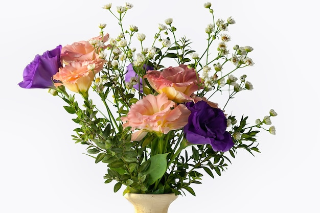 Bouquet of eustoma with twigs of boxwood and small-leaved, isolated on a white background