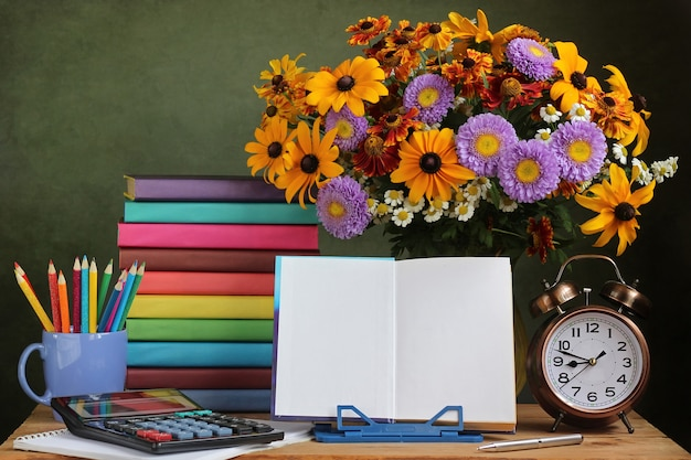 A bouquet of fall flowers, an alarm clock and an open book on a stand.