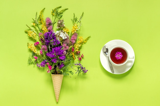 Bouquet field colored flowers in ice cream cone, cup of tea on green paper background
