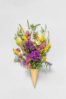 Букет полевых разноцветных цветов в вафельном рожке на сером бумажном фоне. плоская планировка. вид сверху макет концепция день женщин или день матери