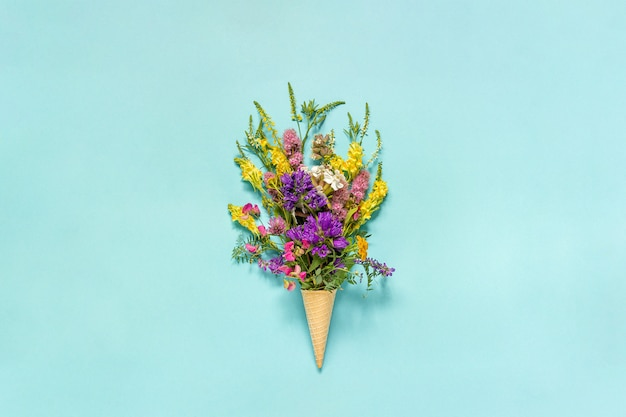 Bouquet field colored flowers in waffle ice cream cone on blue paper background