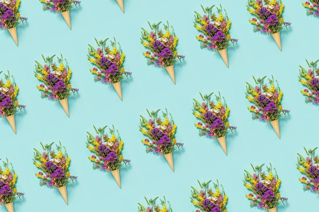 Bouquet field colored flowers in waffle ice cream cone on blue paper