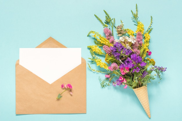 Bouquet field colored flowers in waffle ice cream cone and craft envelope with empty blank paper card