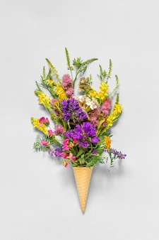 Bouquet field colored flowers in waffle ice cream cone on grey paper background flat lay top view mock up concept women's day or mothers day