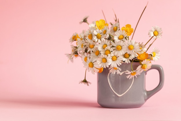 Bouquet of field daisies in a mug on a pink background.
