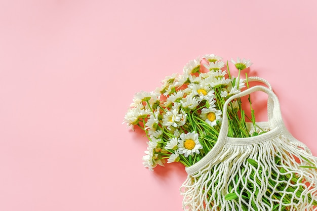 Bouquet of field daisies in reusable shopping eco mesh bag on pink background.