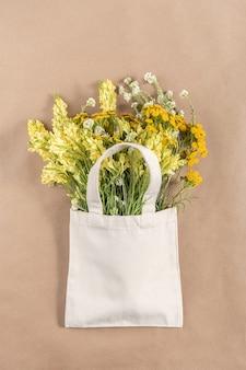 Bouquet of field flowers in fabric eco bag on beige