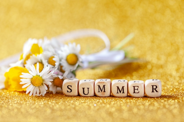 Bouquet flower camomila with text summer on yellow background.